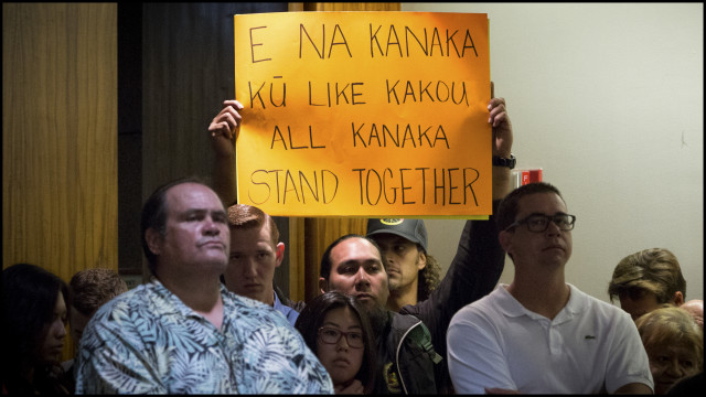 Concerned community member holds up sign during a Department of the Interior panel during a public meeting on whether the United States should establish a government-to-government relationship with Hawaii's indigenous community held at the Hawaii State Capitol auditorium on June 23, 2014