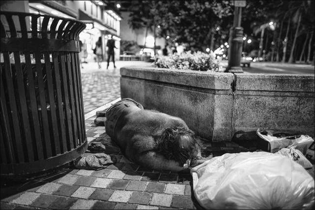 Man sleeping on sidewalk by trash can along Kalakaua Ave. In Waikiki.