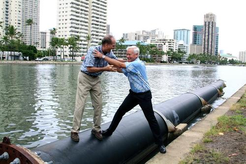Mayor Kirk Caldwell pretends to push a contractor into the Ala Wai Canal during a press conference in 2013 announcing the removal of a faulty sewer pipe.