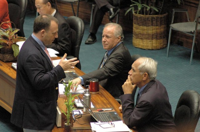 Sen. Josh Green, left, talk to Sens. Russell Ruderman, center, and Mike Gabbard during a floor session in 2015.