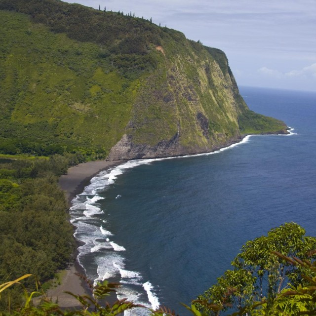 Hawaii's natural beauties, like Waipio Beach on the Big Island, can convince people to move to the islands even when they can't afford to.