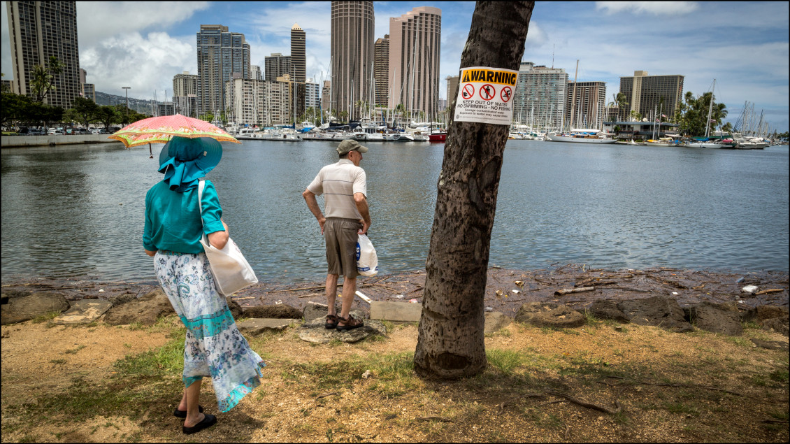 Couple looks out over sewage on Magic Island where the Ala Wai Canal flows out to the ocean in Ala Moana Beach Park on July 22, 2014.