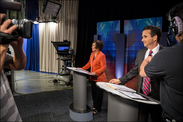 Audio technician adjust's Sen. Brian Schatz's microphone as Rep. Colleen Hanabusa waits for the start of their debate on KITV.