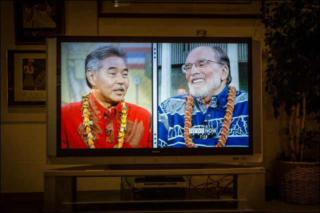 Ige and Abercrombie are seen on TV screen in PBS offices before CD 1 Debate in PBS Studio on July 10, 2014