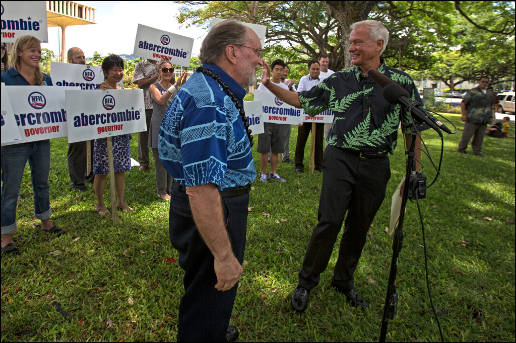 Due to the camera angle, Mayor Kirk Caldwell appears to be touching Gov. Neil Abercrombie's nose but in reality is waving to supporters standing behind them Monday.