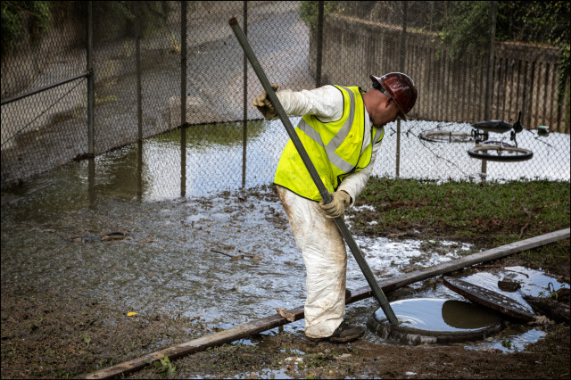 City worker tries to unplug sewer blockage in Palolo in July 22.14