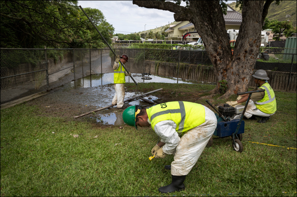 City workers try to unplug a sewer blockage in Palolo on Tuesday. About 100,000 gallons of sewage flowed into the stream, prompting officials to post signs along the Ala Wai Canal and Magic Island warning people to stay out of the water and not fish.
