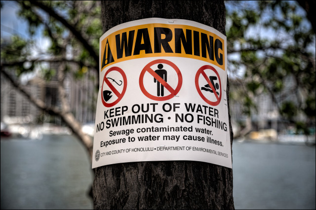 Warning sign on Magic Island where the Ala Wai Canal flows out to the ocean in Ala Moana Beach Park on July 22, 2014.
