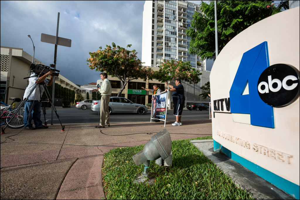 KITV reporter Paul Drewes does a live stand-up for the 6 p.m. news as Honolulu City Councilman Ikaika Anderson waves to motorists before a Wednesday debate in the KITV studios featuring the seven Democratic candidates — including Anderson — for the Congressional District 1 seat.