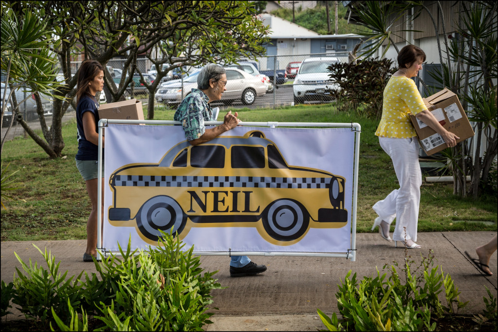 A volunteer at the Lanakila Multi-Purpose Senior Center helps Abercrombie supporters carry a taxi sign into a Candidates Fair held inside the center Friday.