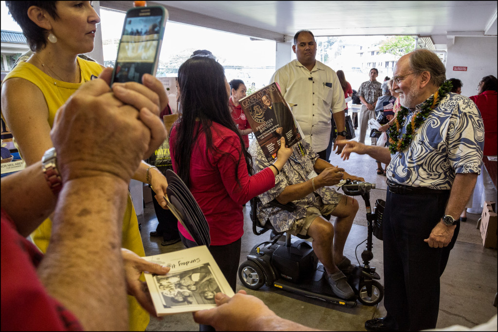 Gov. Neil Abercrombie speaks with a senior at the Candidates Fair as a photo is being taken on an iPhone, while a pamphlet from the Will Espero for Congress camp is passed along, while the governor's security looks on, while Deidre Tegarden, the governor's protocol officer, talks to someone out of frame at the Candidates Fair on Friday.