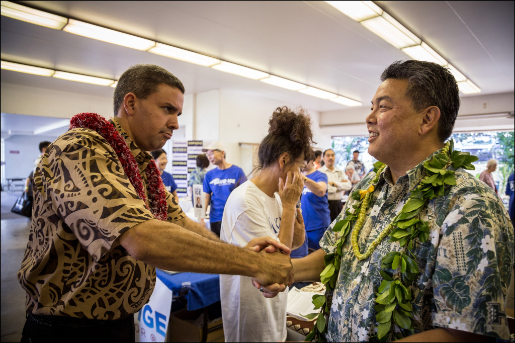 Congressional candidate and City Councilman Ikaika Anderson, left, shakes hands vigorously with a fellow congressional candidate, state Rep.Mark Takaia, at the Candidates Fair on Friday.