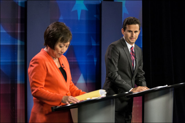 Checking it Out. Brian Schatz takes a look at Colleen Hanabusa's briefing book just before airtime of their televised debate in the KITV studios on July 7, 2014.