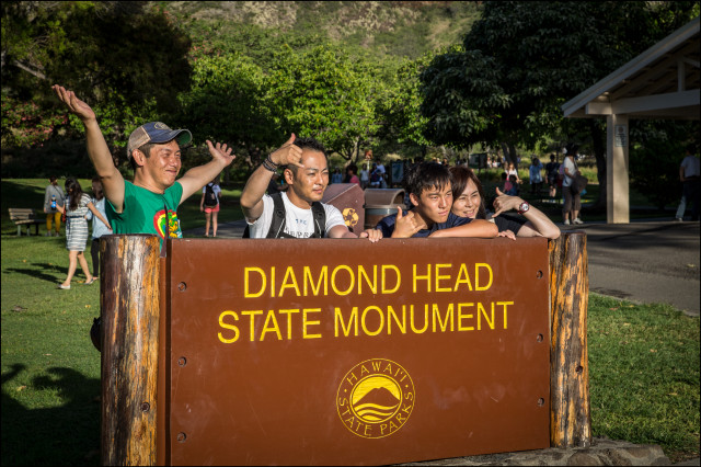 Tourists pose for picture at the entrance to Diamond Head State Monument on July 24, 2014