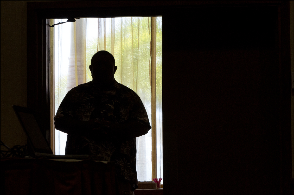 A member of Gov. Neil Abercrombie's security detail stands watch in the doorway of the King Kamehameha Hotel ballroom in Kailua-Kona where the governor debated Sen. David Ige on July 29.