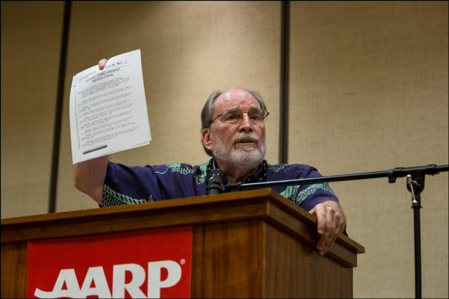 Gov. Neil Abercrombie holds up a bill regarding caregivers  during debate presented by AARP at the King Kamehameha Hotel in Kailua-Kona on July 29, 2014