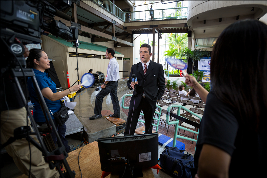 On a very hot and humid afternoon, television reporter Andrew Pereira gets fanned by two Abercrombie staff members as he prepares for his live 5 p.m. broadcast.