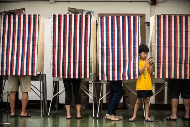 Young guy plays video games as his mom votes at Central Middle School on August 9, 2014