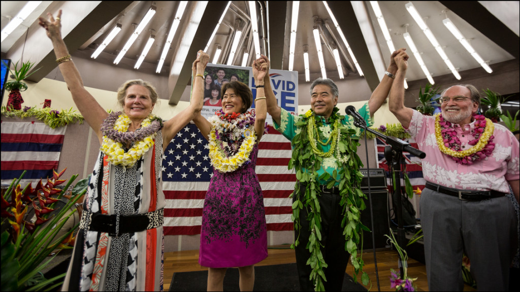 Left to Right: Nancie Caraway, Dawn Ige, Sen. David Ige and Gov. Neil Abercrombie all raise hands at Ige campaign headquarters after Ige beat Abercrombie in the state Primary on August 9, 2014.