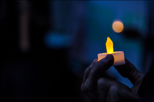 LIGHTING THE NIGHT LED candle during evening protest against HECO's solar policy outside HECO offices on Ward Ave on August 25, 2014