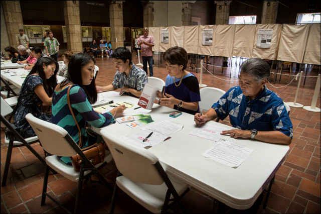 Sen. David Ige, with wife Dawn and three children left to right, Amy, Lauren and Matthew fill out forms to vote early at Honolulu Hale on August 5, 2014