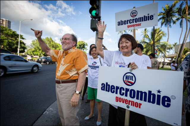 Honolulu City Councilmember Ann Kobayashi sign waves with Gov. Abercrombie at the corner of South King and Ward before his last campaign rally of the Primary season on August 5, 2014.