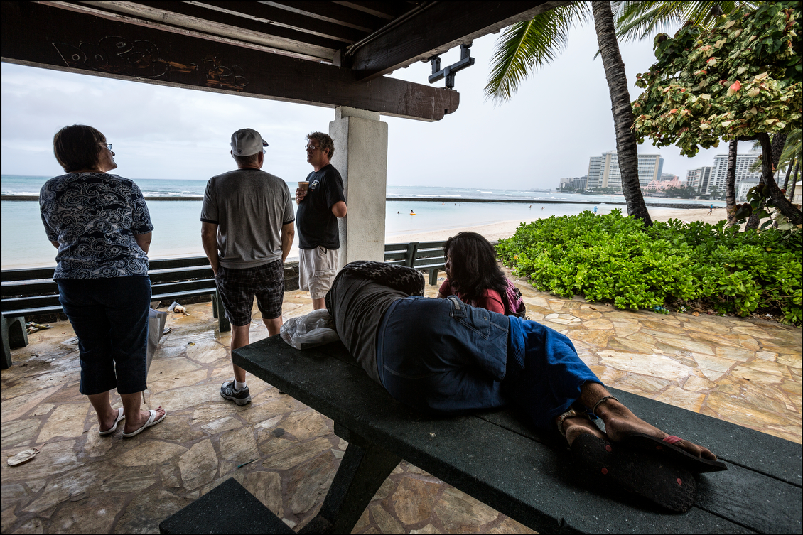 Tourists and homeless wait out rain showers in Waikiki as Oahu waits for tropical storm Iselle on August 8, 2014.