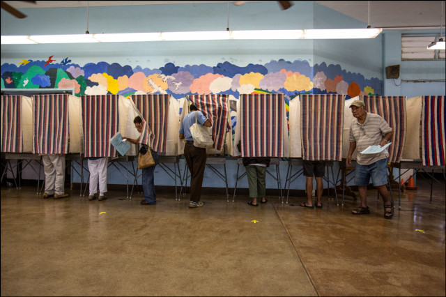 Voters come in and out of booths at Aina Haina Elementary School Primary Day August 9, 2014