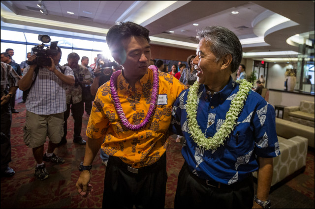 Lt. Gov. Shan Tsutsui and Democratic nominee for Gov. Sen. David Ige walk throughout the media gauntlet as they walk arm and arm into the Democratic Party Unity Breakfast on August 10, 2014