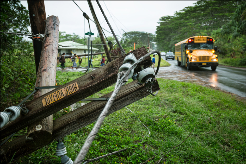 School children walk over downed power lines to board bus in the Paradise Park section of Puna on August 12, 2014.