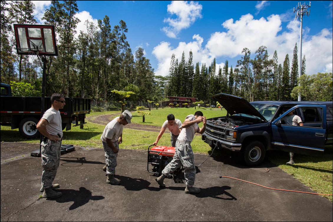 Using old-fashioned muscle and a truck motor, Hawaii Air National Guard personnel power up a generator so residents could charge cell phones and computers.