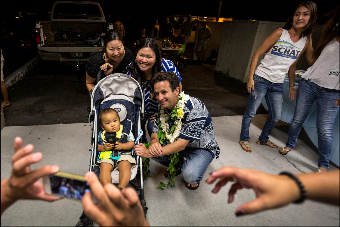 Before leaving for the airport, Schatz posed for an iPhone snap with supporters and a child.