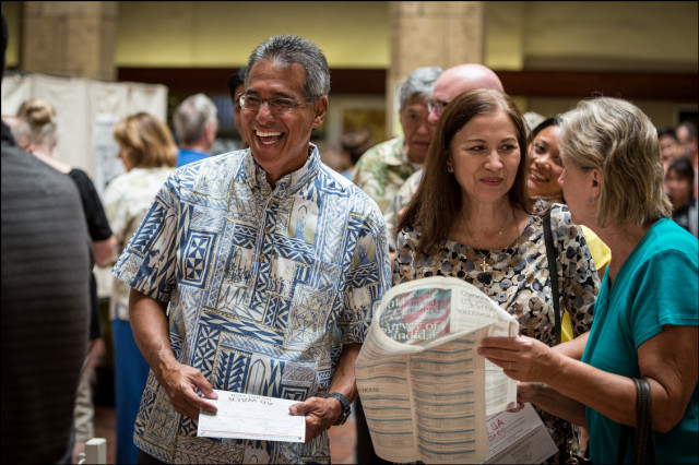 Former Lt. Gov. Duke Aiona and wife Vivian talk to fellow early voters while in line at Honolulu Hale on August 6, 2014.