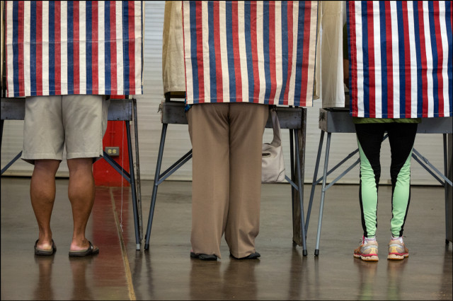 Three people vote at Kalani High School on Primary Day August 9, 2014