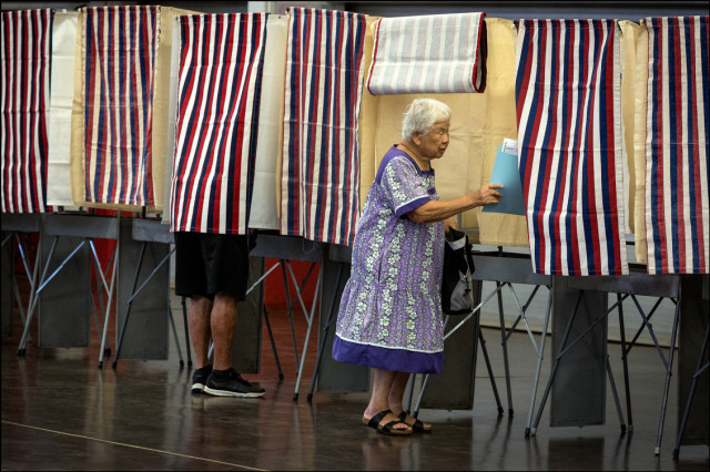Woman goes into voting booth at Kalani High School Primary Day 8.9.14
