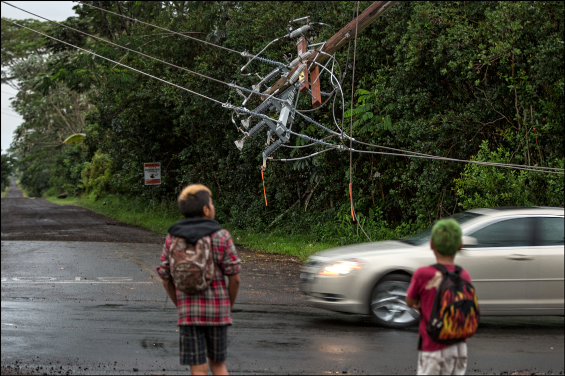 In the Paradise Park section of Puna on Aug. 12, a pair of kids look for their school bus, while avoiding the treacherous downed power lines across the street. The large number of vehicles used to clear  trees and work on downed power lines slowed down traffic flow in many areas.