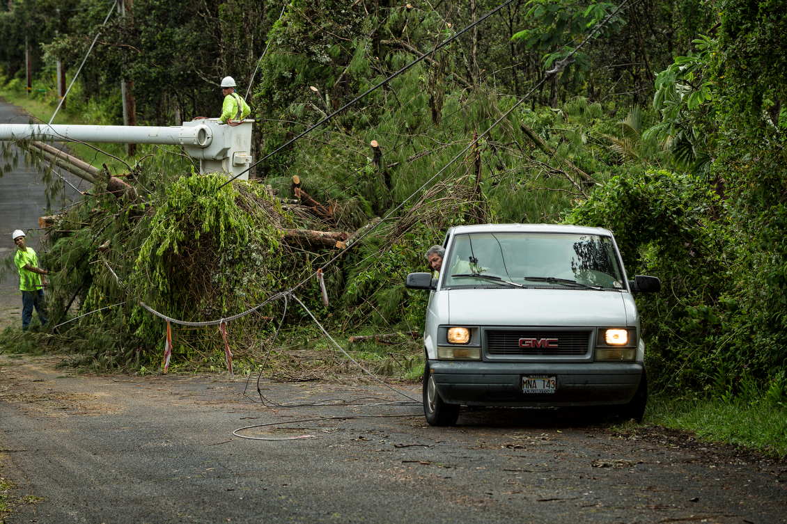 As crews pull fallen trees off of power lines, residents try to navigate their way out of their Nanawale Estates driveway.