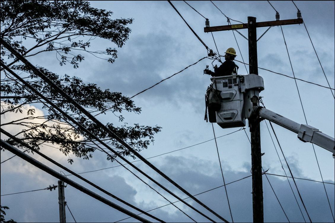 A lineman calculates which wire to work on. By the end of the week, workers had restored power to the majority of those who lost it, although thousands remained without electricity or water.