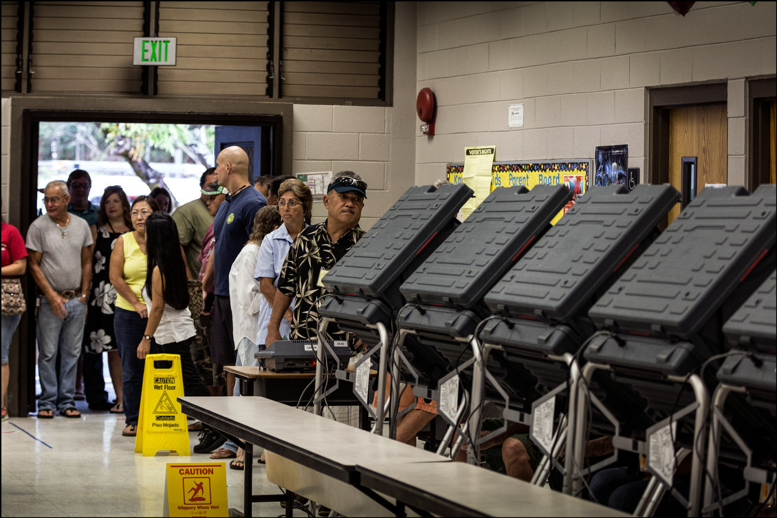 Voters in the Keonepoko Elementary School cafeteria line up to vote on Aug. 15. The vote tally for the day shows that 3,068 people ended up voting, with Schatz gaining 134 votes, leaving him with a 1,769 vote victory.