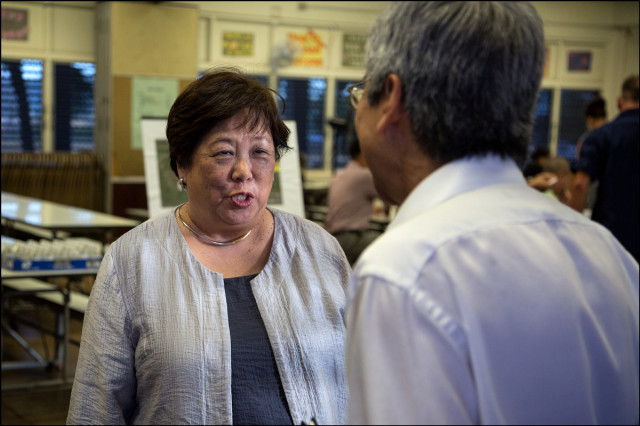 Ember Shinn, Managing Director for the City & County of Honolulu, speaks with Honolulu City Councilmember Breene Harimoto before a public meeting on the proposed Sand Island Housing First Transition Center held in the Pu'uhale Elementary School cafeteria on September 10, 2014