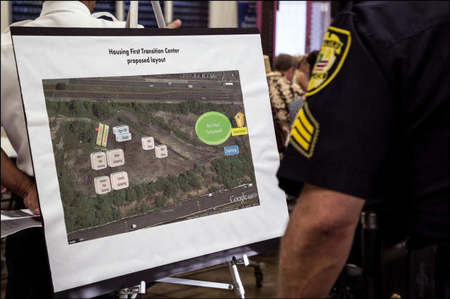 A Honolulu Police officer looks over map before a public meeting on the proposed Sand Island Housing First Transition Center held in the Pu'uhale Elementary School cafeteria on September 10, 2014