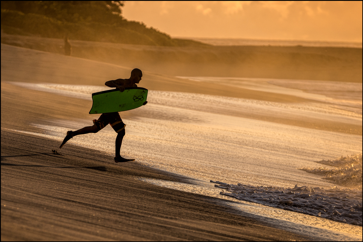 Charging down the beach in fins, a bodyboarder takes aim at the surf during the last days of summer at Sandy Beach on Sept. 16.