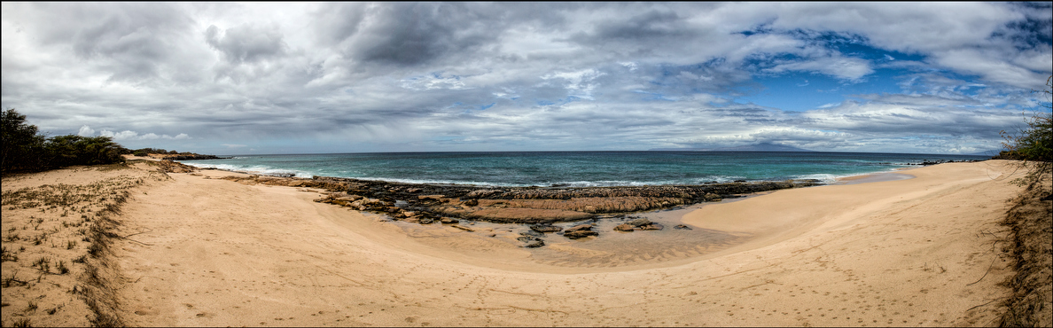 A Kahoolawe beach undisturbed except by cat paw prints.