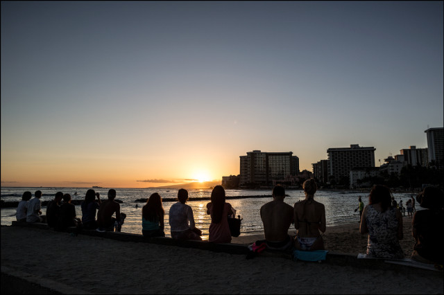 Tourists soak in another Waikiki sunset.