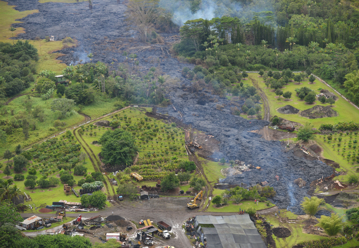 Today's aerial view of molten lava moving from mauka, left of photograph) to rigth,skirting through some structures along a slow approach to Pahoa Village Road. 29 October 2014. photo Cory Lum.