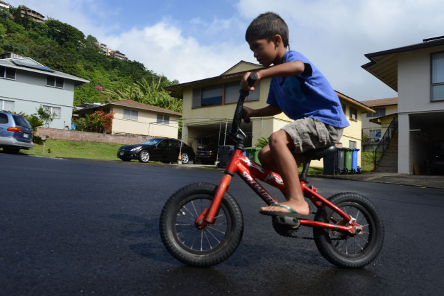 Left, 5-year-old Katin Tilton enjoys a morning bike ride in their cul de sac off of Booth Road in Pauoa Valley.  29 nov 2014.  photograph by Cory Lum