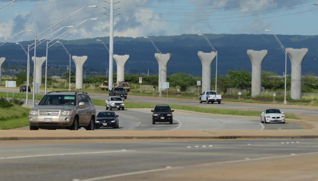 Vehicles head down Kualakai Parkway near Kapolei with concrete rail (foundations) in the background.  Kapolei, Hawaii. 14 November 2014. photograph Cory Lum