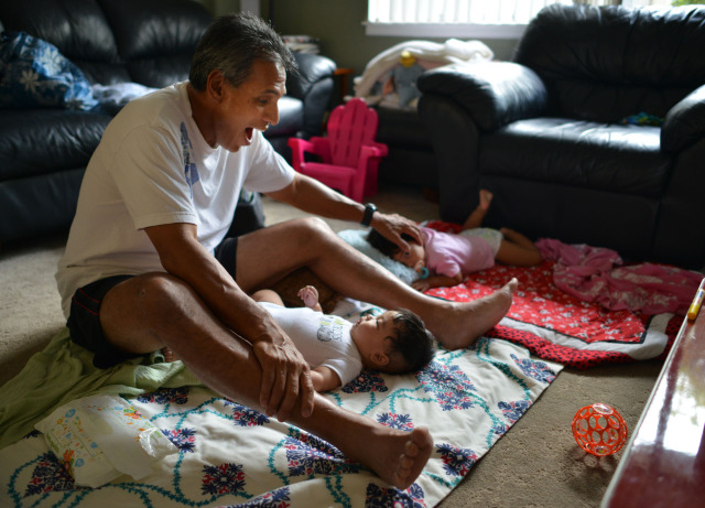 Duke Aiona sits with his two grandkids, 5-months-old Makana John Paul Aiona  and right, 21-months-old Rylee (cq) Bautisto (cq) at his residence in Kapolei.  The two kids just got up after a 45-minute nap.  14 Nov 2014. photo Cory Lum.