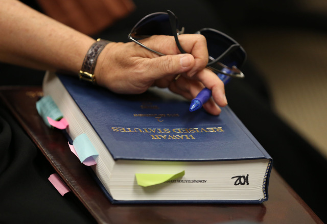 A member of the Attorney General's office has their hands on the Hawaii Revised Statutes during Hawaii State Ethics Commission Conference room held at 1001 Bishop Street, suite 960.  19 nov 2014 . photograph by Cory Lum.