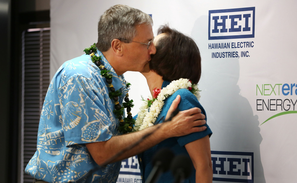 Jim Robo Chairman and CEO, NEXTERA Energy, Inc. gives Connie Lau, President and CEO Hawaiian Electric Industries a kiss before speaking at press conference announcing a merger with NEXTERA at suite 800, 1001 Bishop Street. Honolulu, Hawaii.  3 dec 2014. photograph by Cory Lum